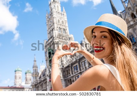 Young female tourist making heart shape with hands on the town hall building background in Munich. Having a great vacation in Germany #502830781