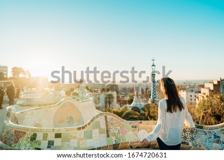 Young female tourist spending vacation in Barcelona,Catalonia,Spain.Traveling to Europe,visiting Parc Guell UNESCO site famous historical landmarks.Panoramic view on entrance.Best sunrise in Barcelona Photo stock ©