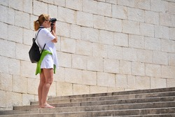 Young female tourist visiting Mediterranean old town on vacation. Woman taking photos on the street