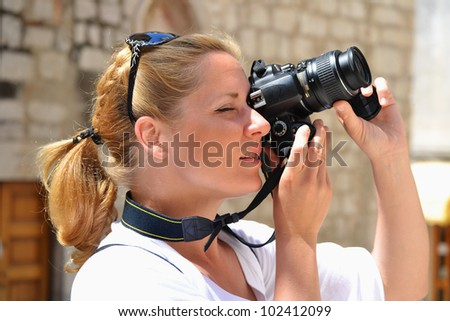 Young female tourist visiting Mediterranean old town on vacation. Woman taking photos on the street - stock photo