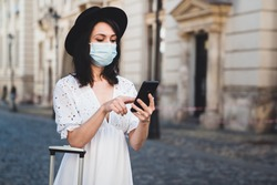Young female tourist wearing a hat and a white dress using phone against old buildings. Woman traveler with protective face mask looking for directions. Epidemic travel concept