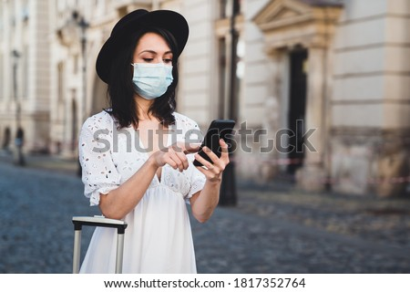 Young female tourist wearing a hat and a white dress using phone against old buildings. Woman traveler with protective face mask looking for directions. Epidemic travel concept Сток-фото ©