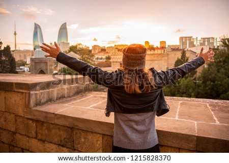Young female tourist with raised hands meets the sunset and stands on the background of Baku city, capital of Azerbaijan. Great vacation in Baku, Azerbaijan.