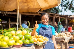 young female trader standing on her stall doing a thumbs up sign excited  smiling to the camera