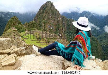 Young female traveler admiring the Inca ruins of Machu Picchu, one of the New Seven Wonder of The World, Cusco Region, Urubamba Province, Peru #1162452547