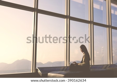 Young female traveler is sitting in modern airport interior and connecting to free wireless for make hotel booking in city of arrival. Silhouette of woman is using digital tablet and waiting her fly