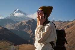 Young female traveler talking on the phone and smile in the mountains
