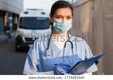 Young female UK EMS doctor in front of healthcare ICU facility,wearing protective face mask holding medical patient health check form,Coronavirus COVID-19 pandemic outbreak crisis PPE shortage