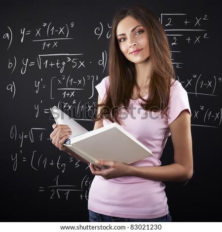 young female university student against blackboard