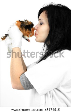 Young female veterinarian holding a guinea pig and kissing it