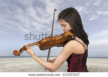 young female violin player outdoors at the beach