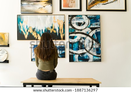 Young female visitor looking reflective while sitting on a bench and admiring the various paintings on the wall of an art gallery Foto stock ©