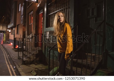 Young female walking lost and alone in a dark scary street alley. Cinematic dark alley.