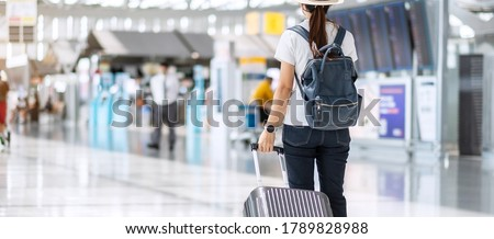 Young female wearing face mask with luggage checking flight time in airport, protection Coronavirus disease infection, Asian woman traveler ready to travel. New Normal and travel under COVID-19
