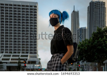 young female wearing medical mask in modern city street, stylish trendy girl with blue hair wearing fashionable protective medical mask amid coronavirus fears, covid19 pandemic, new fashion concept