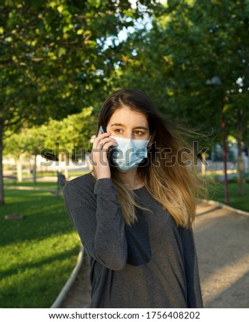 Young female wearing surgical face mask talking on the phone at the park during coronavirus outbreak. Global COVID-19 pandemic concept image. New normal lifestyle for prevention of spreading COVID-19