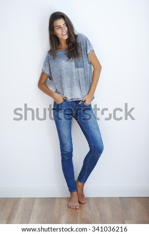 Young female with bare feet and hands in pockets