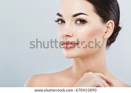 Young female with clean fresh skin, antiaging concept. Attractive girl with naked shoulders, looking at camera and smiling, holding hands near face, lifting arrows under eye