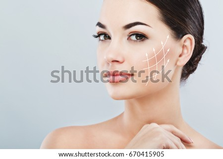 Young female with clean fresh skin, antiaging concept. Attractive girl with naked shoulders, looking at camera and smiling, holding hands near face, lifting arrows lattice #670415905