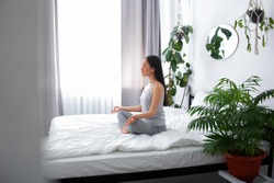 Young female with closed eyes is sitting on bed and doing meditation in lotus position