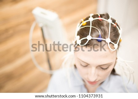 Young female with electrode equipment on her head having clinical test in hospital