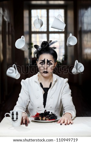 Young female with pierrot style makeup is sitting near the table with cups flying around her
