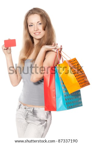 Young female with shopping bags holding blank credit card isolated on white background