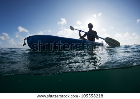 young female with sunglasses on paddling a kayak