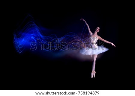 Young female / woman / girl ballerina in a white pack / tutu solo dancing doing stand on toes and leaves blue light leak trail of silhouette in black scene with reflecting floor and dark background #758194879