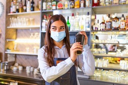 Young female worker at bartender desk in restaurant bar preparing coctail with shaker. Beautiful young woman behind bar wearing protective face mask