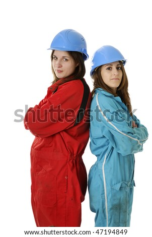 young female workers with helmet standing back against back whit helmets and overalls on white background