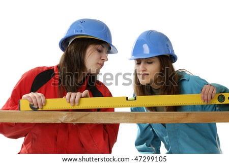 young female workers with protection helmets and overalls on white background
