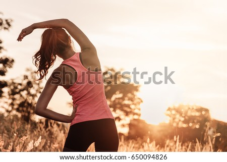 Young female workout before fitness training session at the park. Healthy young woman warming up outdoors. She is stretching her arms and looking away,hi key. - Shutterstock ID 650094826