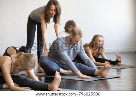 Young female yoga instructor teaching Head to Knee Forward Bend pose, Janu Sirsasana exercise for group of sporty people practicing in studio, working out indoor, correcting beginners, full length
