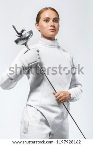Young fencer athlete wearing fencing costume. holding the sword. Isolated on white background