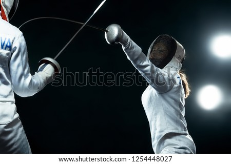 Young fencer athlete wearing mask and white fencing costume. holding the sword on black background with lights.