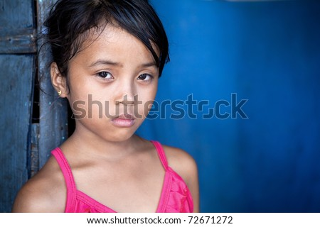stock photo Young Filipina girl 8 years old with sad and somber expression