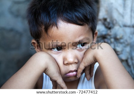 Young Filipino boy portrait against wall - sad expression, poverty