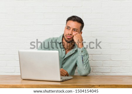Young filipino man sitting working with his laptop who feels sad and pensive, looking at copy space.