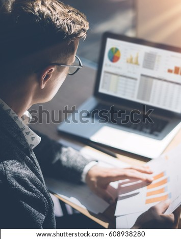Young finance market analyst in eyeglasses working at sunny office on laptop while sitting at wooden table.Businessman analyze document in his hands.Graphs and diagramm on notebook screen.Vertical