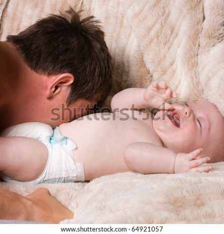Young first time father playing with baby son.