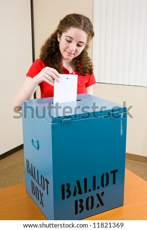Young first time voter dropping her ballot in the box at the polling place.