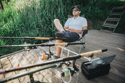 Young fisherman fishing on lake or river. Relaxed sitting in folding chair in front three rods for fishing. Professional fishing equipment. Sitting at edge of lake or river.