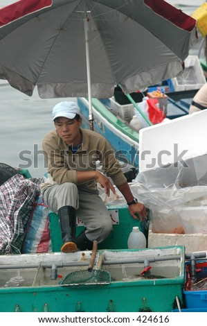 Young fisherman selling his catch from his boat in Hong Kong