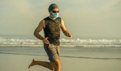 young fit and attractive man in face mask running barefoot on sea training after covid19 lockdown feeling free outdoors in healthy lifestyle concept - New normal beach jogging workout