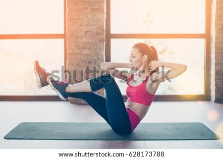 Young fit and beautiful sportswoman is exercising on the mat indoors. She is totally concentrated on her workout #628173788