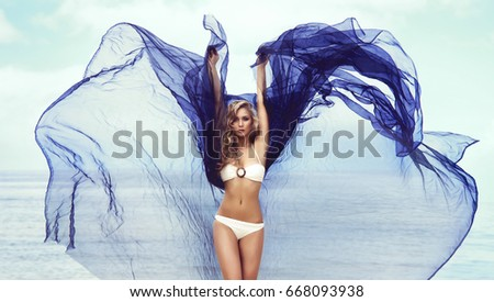 Young, fit and sexy woman dancing with a blowing fabric on a beach.
