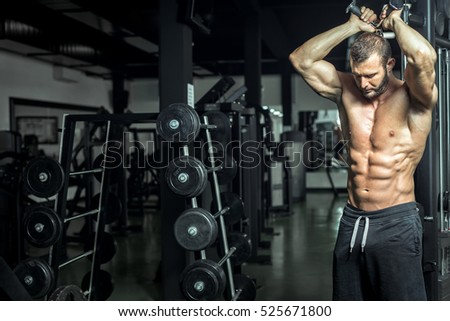 Young fit attractive sexy man doing overhead triceps rope extension exercise in modern fitness center.