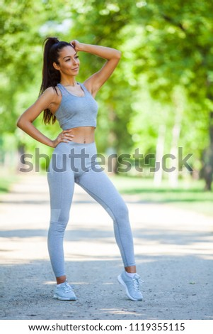 Stock Photo Young fit beautiful girl posing outdoor in her gray sportswear in forest during summer sunny day
