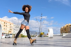Young fit black woman on roller skates riding outdoors on urban street with open arms. Smiling girl with afro hairstyle rollerblading on sunny day
